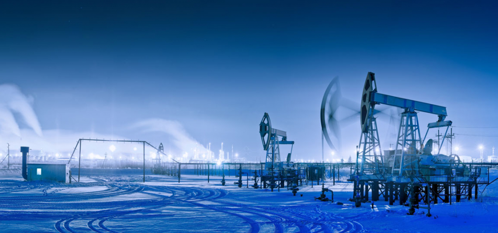 Oil and gas industry. Panoramic of a pumpjack and oil refinery in the winter with snow. Night view.