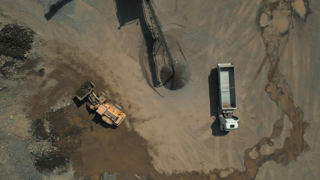 Top view of mining coal. Huge industrial equipment secreting black coal. Wet ground on the background.
