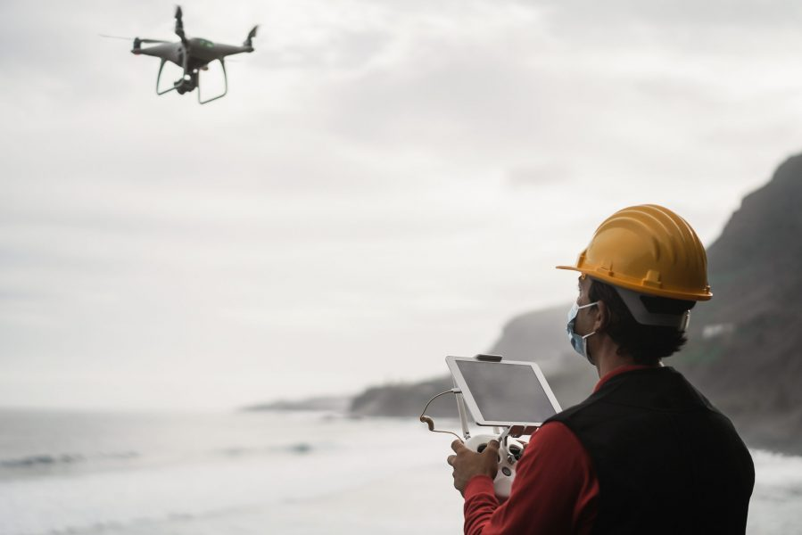 Man engineer flying drone while wearing protective mask during coronavirus outbreak - Focus on tablet