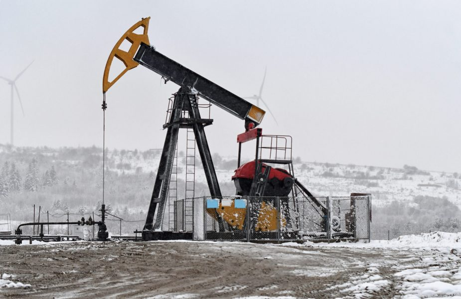 Oil pump. Oil and gas industry equipment. Oil field pump jack and oil refinery in the winter with snow, wind turbine mountains and forest in background