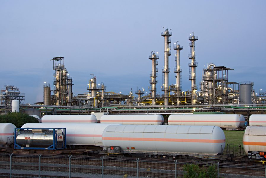 Some cargo trains in front of a chemical plant.