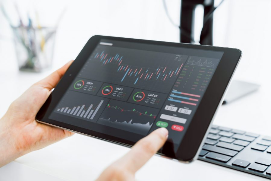 Stock exchange market concept, Hand trader touch on digital tablet with graphs analysis candle line on the table in house, diagrams on screen.