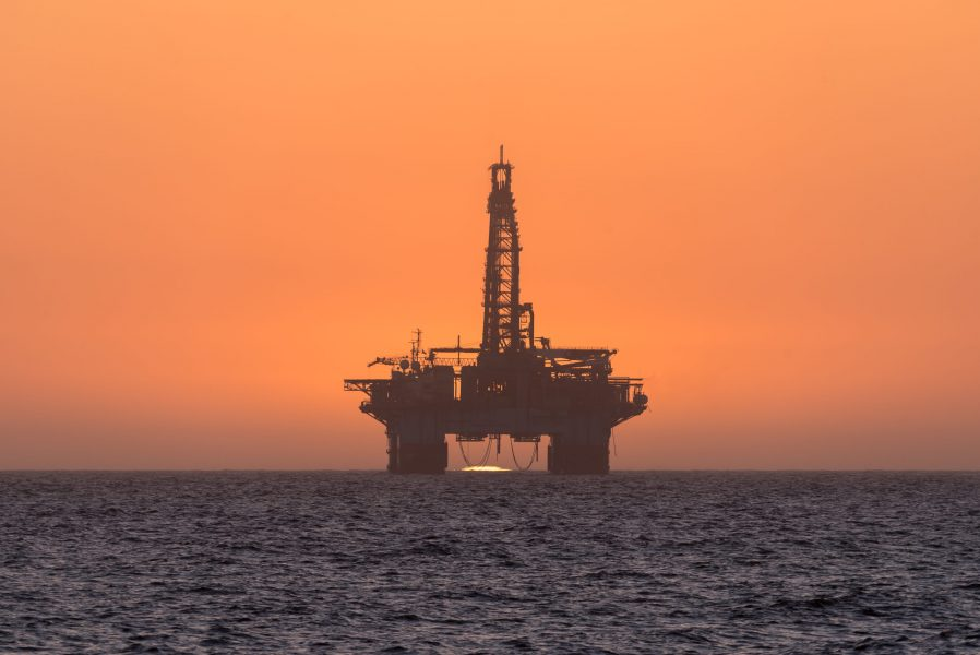 The sun is setting behind an oil drilling platform anchored in the Atlantic Ocean at Longbeach in the Namib Desert of Namibia